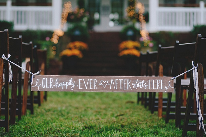 We LOVE this hand lettered aisle sign for this gorgeous DIY wedding!