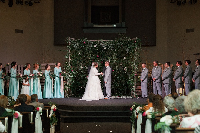 We're loving the gorgeous greenery and floral backdrop behind this gorgeous wedding ceremony!
