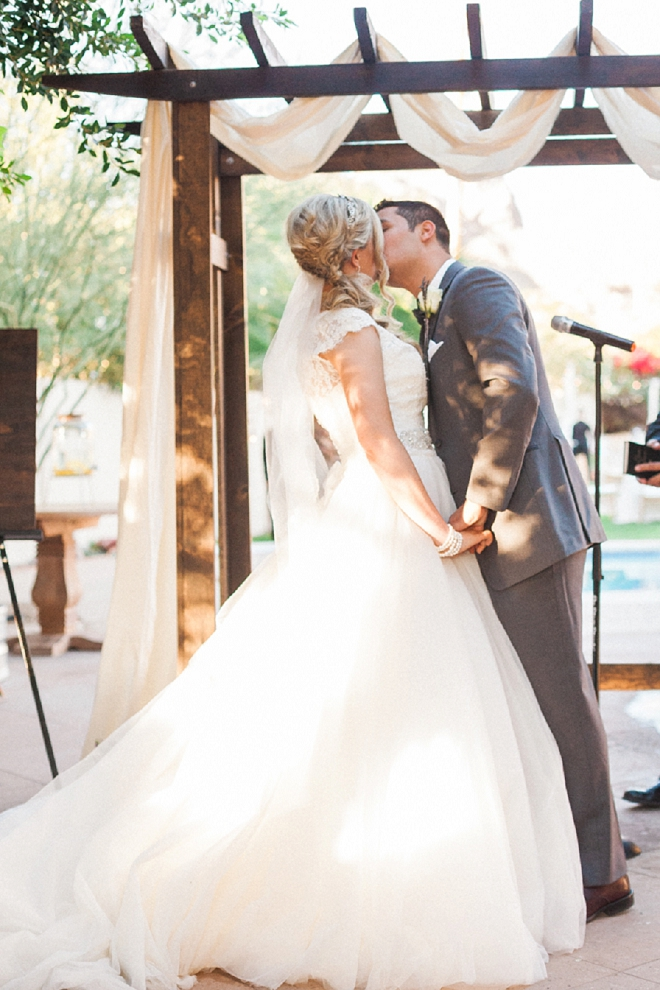 Swooning over this sweet outdoor desert ceremony and first kiss and Mr. and Mrs!