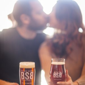 Darling shot of a beer loving couple kissing during their engagement shoot!