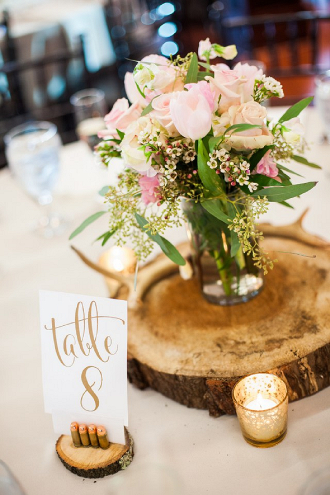 We're loving these handcut wooden centerpices and gold hand lettered table numbers held by bullet casings!