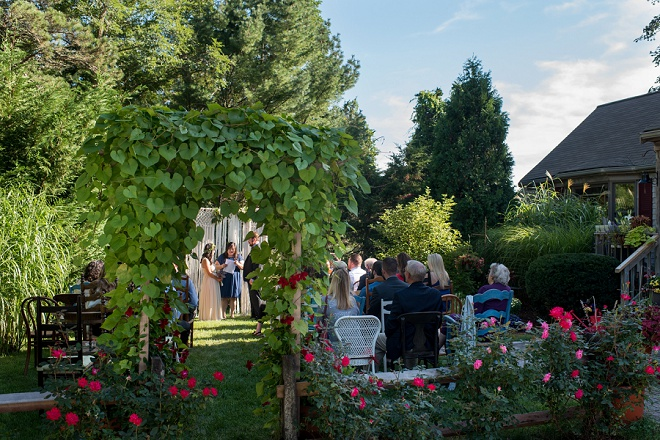 We love this peekaboo ceremony photo of their intimate backyard wedding!!