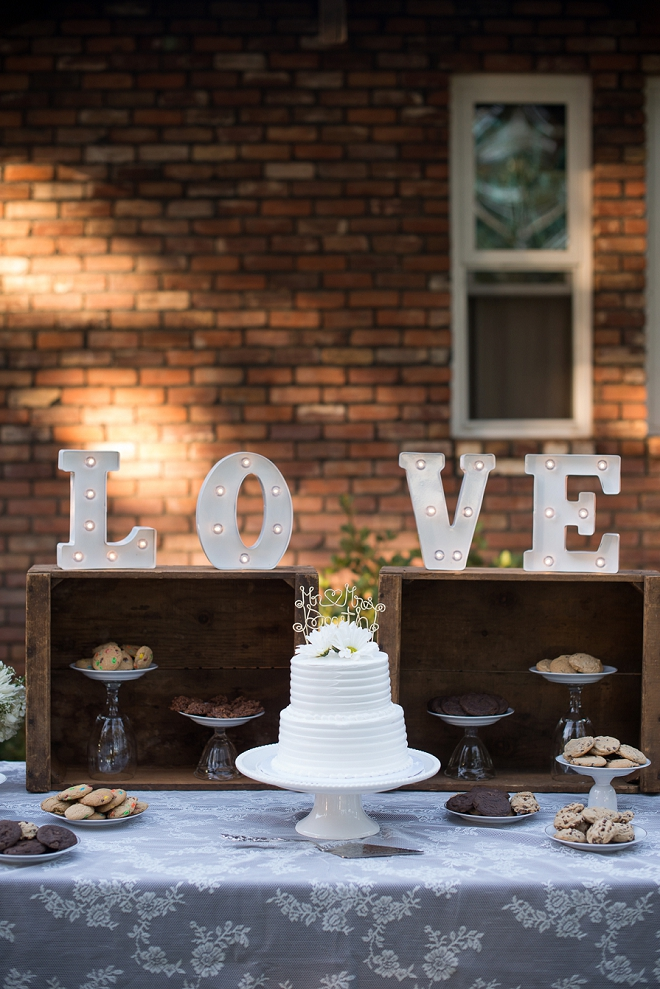 Gorgeous cake and LOVE sign at this couple's outdoor reception!